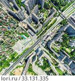 Купить «Aerial city view with crossroads and roads, houses, buildings, parks and parking lots. Sunny summer panoramic image», фото № 33131335, снято 29 марта 2020 г. (c) Александр Маркин / Фотобанк Лори
