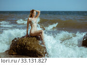 A young woman in a swimsuit sits on the stones in the waves and breeches of the sea or ocean. Стоковое фото, фотограф katalinks / Фотобанк Лори