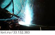 Купить «Welder in protective workwear welds metal details in shop», видеоролик № 33132383, снято 16 февраля 2020 г. (c) Алексей Кузнецов / Фотобанк Лори