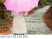 Купить «Young woman with umbrella walking through the park», фото № 33132551, снято 17 февраля 2020 г. (c) PantherMedia / Фотобанк Лори
