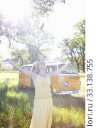 Купить «Young woman with arms outstretched in field by camper van, smiling (lens flare)», фото № 33138755, снято 2 апреля 2020 г. (c) PantherMedia / Фотобанк Лори
