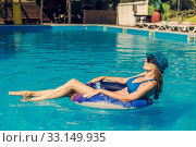 A young woman in a swimsuit and a blue hat and sunglasses swims in a rubber ring in the pool. Стоковое фото, фотограф katalinks / Фотобанк Лори