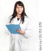 Купить «Doctor woman at work standing on white background, white coat, blue clipboard in hands», фото № 33151379, снято 28 декабря 2014 г. (c) Кекяляйнен Андрей / Фотобанк Лори