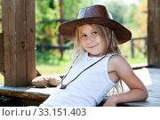 Preschool girl dressed sleeveless sports shirt and brown cowboy hat sitting on wooden porch of timber house. Стоковое фото, фотограф Кекяляйнен Андрей / Фотобанк Лори