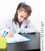 Купить «Cute preschool girl playing doctor, dressed uniform sitting at the table and writing in clipboard, white background», фото № 33151427, снято 28 декабря 2014 г. (c) Кекяляйнен Андрей / Фотобанк Лори