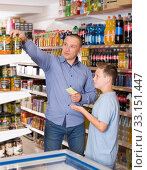 Купить «Young father and son choosing goods in supermarket», фото № 33151447, снято 4 июня 2018 г. (c) Яков Филимонов / Фотобанк Лори