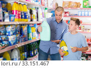 Купить «Family of father with son choosing household chemicals with shopping list», фото № 33151467, снято 4 июня 2018 г. (c) Яков Филимонов / Фотобанк Лори