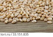 Купить «Pile of delicious pine nuts on a wooden surface», фото № 33151835, снято 6 апреля 2020 г. (c) Яков Филимонов / Фотобанк Лори