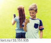 Купить «kids with smartphones playing game in summer park», фото № 33151935, снято 24 июля 2016 г. (c) Syda Productions / Фотобанк Лори