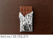 Купить «chocolate bar in foil wrapper on brown background», фото № 33152211, снято 1 февраля 2019 г. (c) Syda Productions / Фотобанк Лори