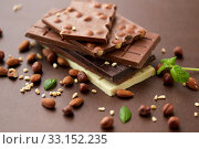 Купить «close up of different chocolate bars and nuts», фото № 33152235, снято 1 февраля 2019 г. (c) Syda Productions / Фотобанк Лори