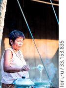 Купить «SUKHOTHAI, THAILAND - MAY 4: Unidentified mature woman is selling Thai traditional snack on May 4, 2013 at Rim Yom 2437 night market, Sukhothai, Thailand.», фото № 33153835, снято 4 мая 2013 г. (c) age Fotostock / Фотобанк Лори