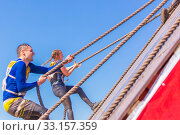 Купить «Russia, Samara, June 2019: a young sports man with the help of a rope overcomes the most difficult obstacles in the race of Everest heroes.», фото № 33157359, снято 8 июня 2019 г. (c) Акиньшин Владимир / Фотобанк Лори
