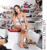 Купить «Woman 20-23 years old is trying on summer shoes in boutique.», фото № 33160271, снято 17 августа 2017 г. (c) Яков Филимонов / Фотобанк Лори