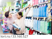 Купить «Woman with girl looking for cleaners in supermarket», фото № 33160527, снято 5 января 2017 г. (c) Яков Филимонов / Фотобанк Лори