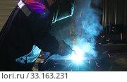 Купить «Professional blacksmith welding metals and using protective mask in industrial shop. Audio included», видеоролик № 33163231, снято 19 февраля 2020 г. (c) Алексей Кузнецов / Фотобанк Лори