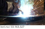 Купить «Bright sparks from welding equipment while the welder is working in an industrial shop», видеоролик № 33163327, снято 19 февраля 2020 г. (c) Алексей Кузнецов / Фотобанк Лори