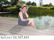 attractive woman siiting with legs in  the pool. Стоковое фото, фотограф Jürgen Hüls / PantherMedia / Фотобанк Лори