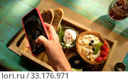 Купить «From above crop hand of female holding smartphone and taking photo of delicious healthy breakfast served on wooden tray on rustic green wooden table», видеоролик № 33176971, снято 19 февраля 2020 г. (c) Ekaterina Demidova / Фотобанк Лори
