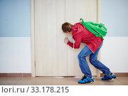 Curious pupil peeping into keyhole of classroom door at school. Стоковое фото, фотограф Dmitriy Shironosov / PantherMedia / Фотобанк Лори