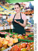 Купить «Young female seller putting fresh goods on shelves in greengrocery», фото № 33180659, снято 14 октября 2017 г. (c) Яков Филимонов / Фотобанк Лори