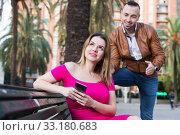 Купить «Young woman is inaccessibility when man is playful talking with her», фото № 33180683, снято 18 октября 2017 г. (c) Яков Филимонов / Фотобанк Лори