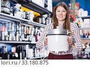 Saleswoman offering slow cooker in household appliances shop. Стоковое фото, фотограф Яков Филимонов / Фотобанк Лори