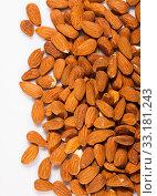 Handful of roasted almond nuts on a white surface. Стоковое фото, фотограф Яков Филимонов / Фотобанк Лори