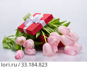 Bouquet of pink tulips and a red box with a gift on a white isolated background. Стоковое фото, фотограф Светлана Валуйская / Фотобанк Лори
