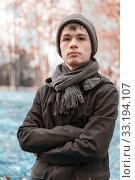 Serious teenage boy in the autumn sunny park. Стоковое фото, фотограф Volha Kavalenkava / PantherMedia / Фотобанк Лори