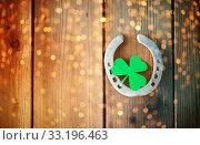 horseshoe with shamrock on wooden background. Стоковое фото, фотограф Syda Productions / Фотобанк Лори