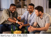 Купить «male friends with smart watch and beer at home», фото № 33196555, снято 28 декабря 2019 г. (c) Syda Productions / Фотобанк Лори