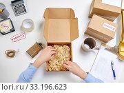 Купить «hands with straw filler in parcel at post office», фото № 33196623, снято 11 января 2019 г. (c) Syda Productions / Фотобанк Лори