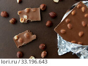 Купить «milk chocolate bar with hazelnuts in foil wrapper», фото № 33196643, снято 1 февраля 2019 г. (c) Syda Productions / Фотобанк Лори