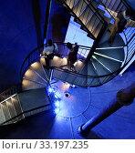 Купить «Германия, Люнебург. Люди спускаются по винтовой лестнице внутри огромного бака выведенной из эксплуатации водонапорной башни. В настоящее время башня используется как музей и смотровая площадка. Необычное освещение, синий цвет», фото № 33197235, снято 8 августа 2015 г. (c) Наталья Николаева / Фотобанк Лори