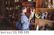 Купить «Portrait of young female customer visiting pottery shop», видеоролик № 33198335, снято 31 мая 2020 г. (c) Яков Филимонов / Фотобанк Лори