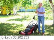 Купить «Positive elderly man with lawnmower when mowing the lawn», фото № 33202735, снято 25 июня 2019 г. (c) Татьяна Яцевич / Фотобанк Лори