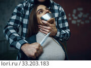 Maniac kidnapper scares his victim with a knife. Стоковое фото, фотограф Tryapitsyn Sergiy / Фотобанк Лори
