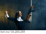 Купить «Young nun in a cassock holds assault rifle», фото № 33203259, снято 14 ноября 2019 г. (c) Tryapitsyn Sergiy / Фотобанк Лори