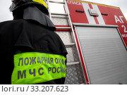 Купить «Сотрудник пожарного расчета стоит у пожарной машины во время показательного смотра пожарной техники в честь 30 летия МЧС на ВДНХ в городе Москве, Россия», фото № 33207623, снято 23 февраля 2020 г. (c) Николай Винокуров / Фотобанк Лори