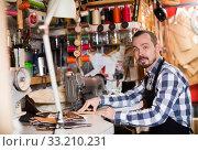 Купить «Young man worker neatly stitching belt», фото № 33210231, снято 12 июля 2020 г. (c) Яков Филимонов / Фотобанк Лори