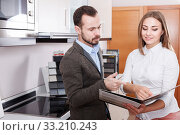 Young competent female seller consulting male customer in store. Стоковое фото, фотограф Яков Филимонов / Фотобанк Лори