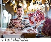 Seller offering sliced bacon. Стоковое фото, фотограф Яков Филимонов / Фотобанк Лори