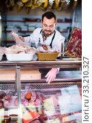 Купить «Male shop assistant demonstrating sausages in butcher's shop», фото № 33210327, снято 2 января 2017 г. (c) Яков Филимонов / Фотобанк Лори
