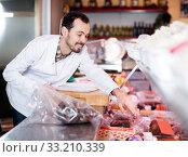 Smiling male seller showing tasty sausages. Стоковое фото, фотограф Яков Филимонов / Фотобанк Лори