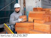 Man stacking red bricks. Стоковое фото, фотограф Яков Филимонов / Фотобанк Лори