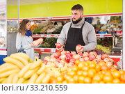 Купить «Positive man in apron selling ripe pomegranates», фото № 33210559, снято 20 ноября 2019 г. (c) Яков Филимонов / Фотобанк Лори