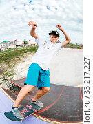 Купить «Teen skater hang up over a ramp on a skateboard in a skate park. Wide angle», фото № 33217227, снято 7 июля 2020 г. (c) easy Fotostock / Фотобанк Лори