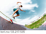 Купить «A young skater jumps from a ramp down when an unsuccessful attempt to do a trick in a skatepark», фото № 33217535, снято 7 июля 2020 г. (c) easy Fotostock / Фотобанк Лори