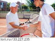 Купить «mature senior and young man shake hands before tennis match», фото № 33227235, снято 29 июля 2019 г. (c) Татьяна Яцевич / Фотобанк Лори